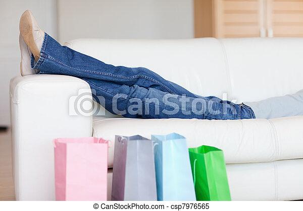 La mujer se relaja en el sofá después de ir de compras - csp7976565