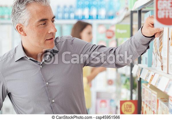 Un hombre comprando en el supermercado - csp45951566