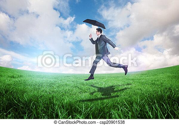 Una imagen compuesta de hombre de negocios saltando sosteniendo un paraguas - csp20901538