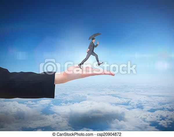 Una imagen compuesta de hombre de negocios saltando sosteniendo un paraguas - csp20904872