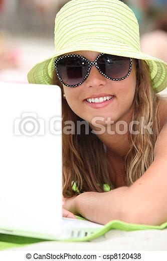 Una joven con su portátil en la playa - csp8120438
