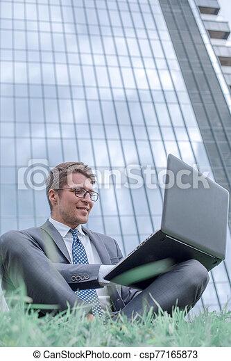 computador portatil, oficina, hombre de negocios, sentado, edificio, utilizar, pasto o césped - csp77165873