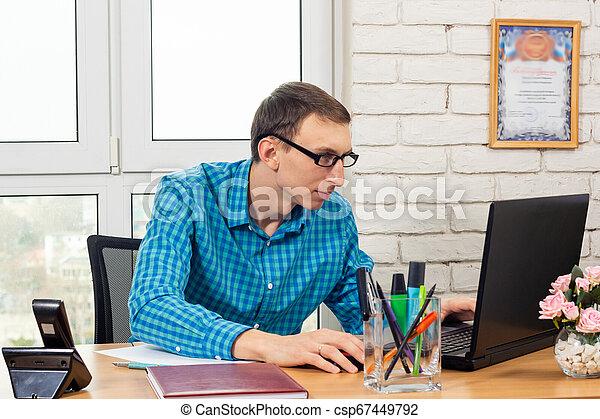 Trabajador de oficinas trabajando en un portátil - csp67449792