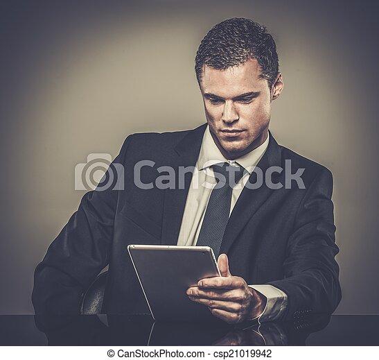 Hombre bien vestido con traje negro con tablet pc - csp21019942