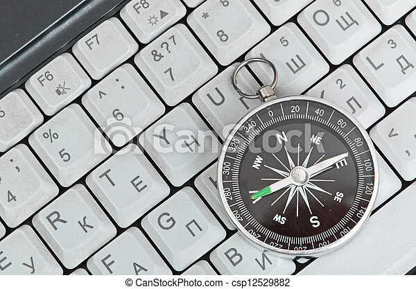 Computer keyboard and retro compass, business decision - csp12529882