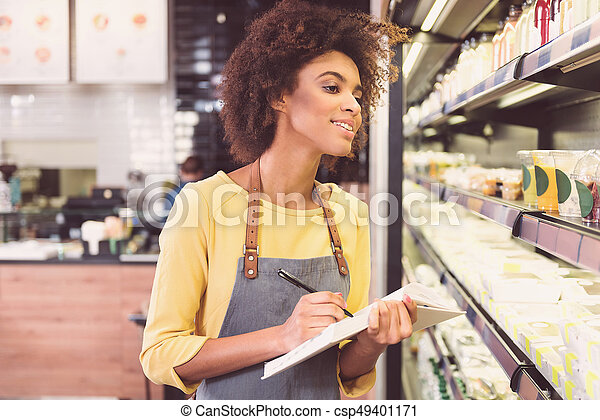 La Chica Concentrada Positiva Est Comprobando El Producto