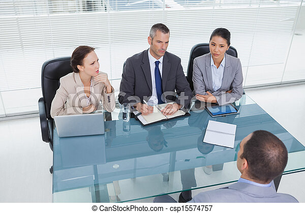Concentrated business team interviewing experienced man - csp15574757