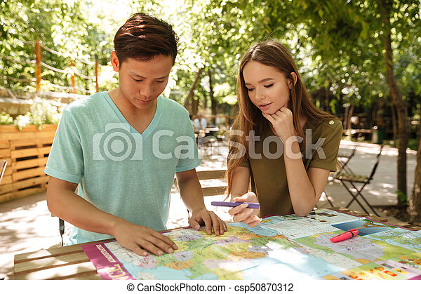 Concentrated couple sitting outdoor - csp50870312