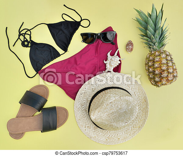 concept of summer vacation with beach accessories and a pineapple on yellow - csp79753617