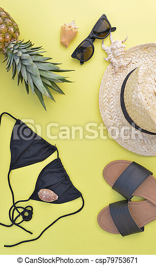concept of summer vacation with beach accessories and a pineapple on yellow background - csp79753671