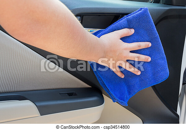 Concept of Woman hand cleaning interior car door panel with microfiber cloth. - csp34514800