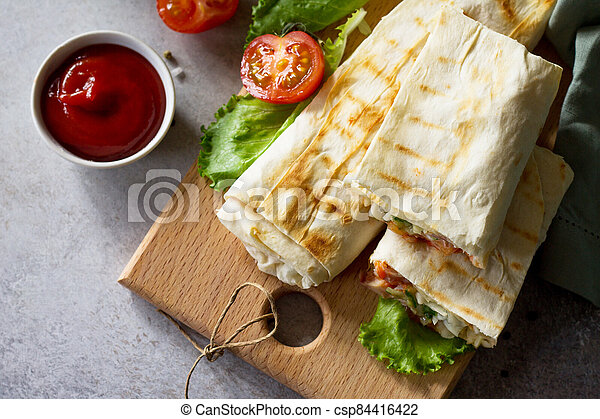 Concept restaurant fast food. Shawarma pita bread with grilled chicken, shaurma doner, fresh vegetables and cream sauce on a light stone background. Top view flat lay background. - csp84416422