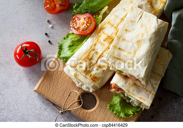 Concept restaurant fast food. Shawarma pita bread with grilled chicken, shaurma doner, fresh vegetables and cream sauce on a light stone background. Top view flat lay background. - csp84416429