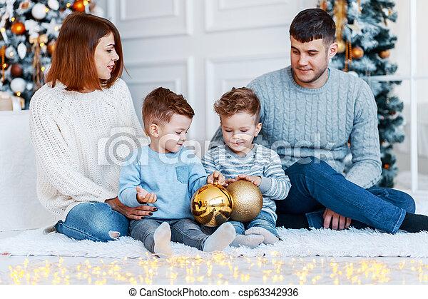 Una familia de cuatro abrazados frente al árbol de Navidad. Amor, felicidad y un gran concepto familiar - csp63342936