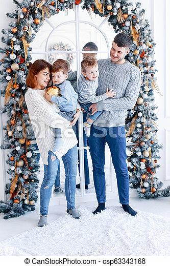Una familia de cuatro abrazados frente al árbol de Navidad. Amor, felicidad y un gran concepto familiar - csp63343168