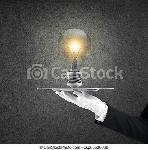 Camarero que sostiene una bandeja con una bombilla. Concepto una gran idea - csp65536060