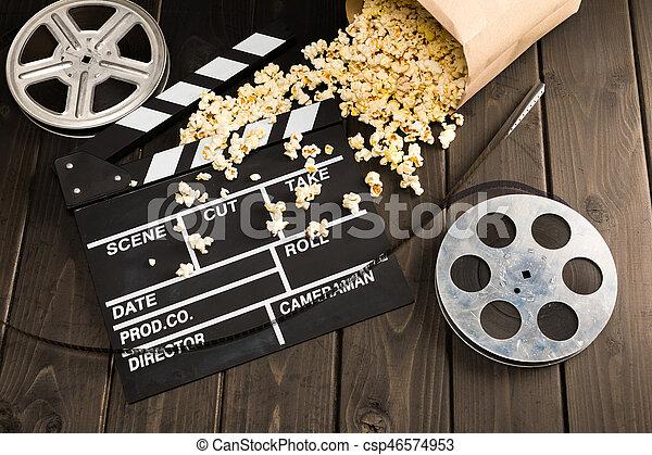 Vista cercana a las palomitas de maíz en contenedor de papel y placa de claque de cine en la mesa, concepto de hora de la película - csp46574953