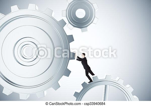 Para hacer un concepto de trabajo de negocios con empresarios girando engranajes - csp33940684