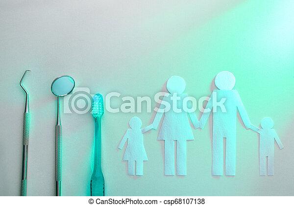 Concepto dental de la familia en la mesa blanca con luz verde - csp68107138