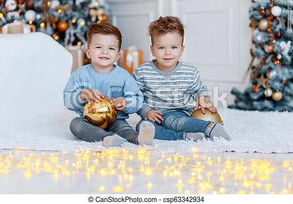 Hermanos gemelos frente al árbol de Navidad con velas y regalos. Amor, felicidad y un gran concepto familiar - csp63342934