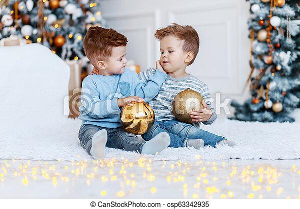 Hermanos gemelos frente al árbol de Navidad con velas y regalos. Amor, felicidad y un gran concepto familiar - csp63342935