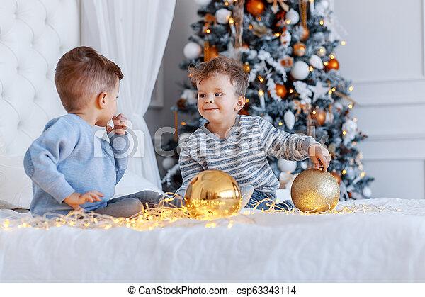 Hermanos gemelos frente al árbol de Navidad con velas y regalos. Amor, felicidad y un gran concepto familiar - csp63343114