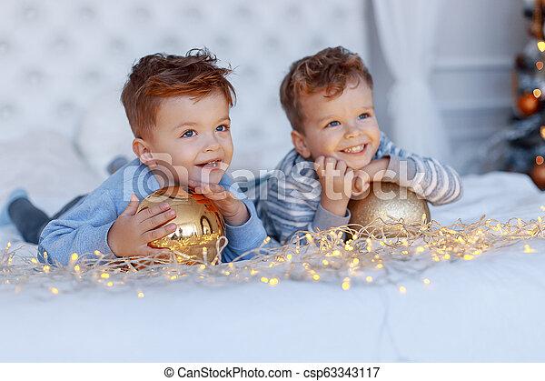 Hermanos gemelos frente al árbol de Navidad con velas y regalos. Amor, felicidad y un gran concepto familiar - csp63343117