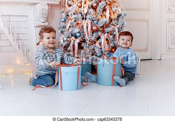 Hermanos gemelos frente al árbol de Navidad con velas y regalos. Amor, felicidad y un gran concepto familiar - csp63343378