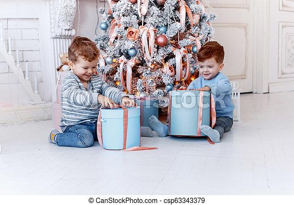 Hermanos gemelos frente al árbol de Navidad con velas y regalos. Amor, felicidad y un gran concepto familiar - csp63343379