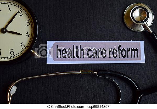 Reforma de Salud en el papel impreso con Inspiración de Concept de Salud. Reloj de alarma, estetoscopio negro. - csp69814397