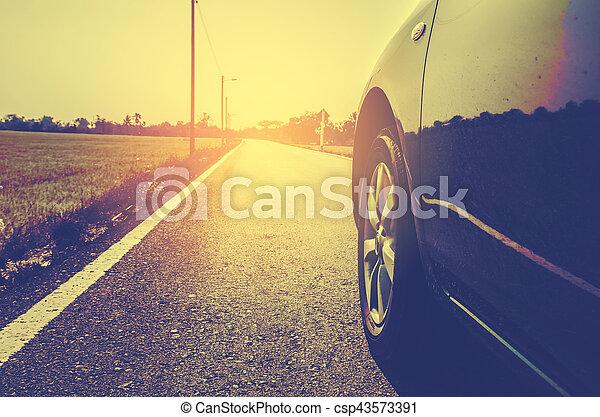 concepto de viaje, vista lateral del coche moderno en la carretera en el campo, color de tono vintage - csp43573391