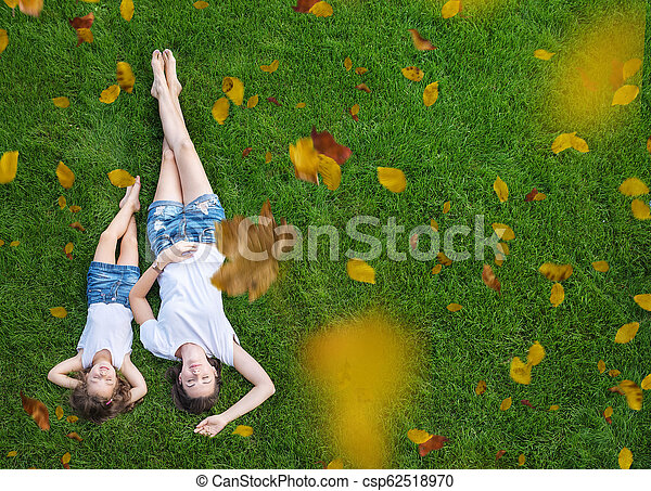 Conceptual portrait of a mother relaxing with daughter on a fresh, green lawn - csp62518970