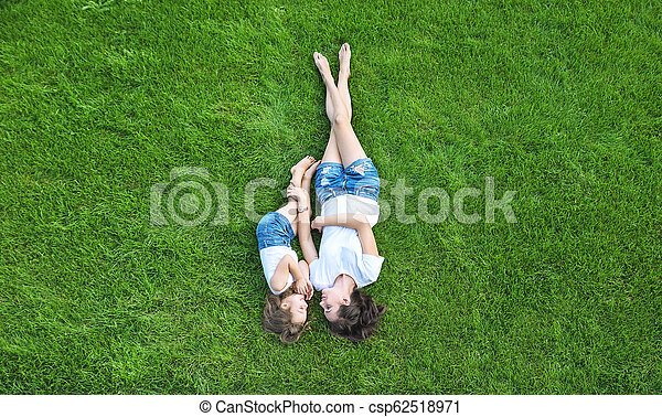 Conceptual portrait of a mother relaxing with daughter on a fresh, green lawn - csp62518971