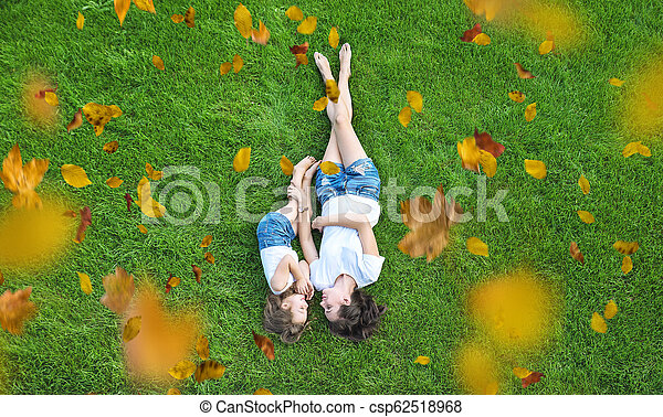 Conceptual portrait of a mother relaxing with daughter on a fresh, green lawn - csp62518968