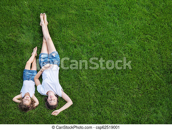 Conceptual portrait of a mother relaxing with daughter on a fresh, green lawn - csp62519001