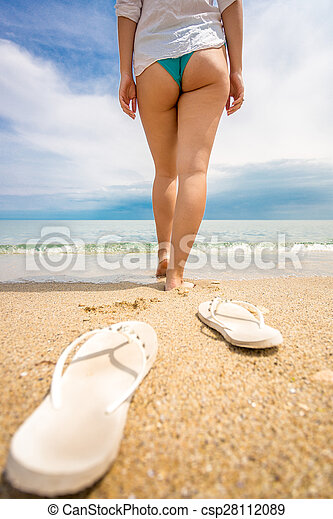 9b75c2913895 Conceptual shot of woman taking of shoes and walking in the sea -  csp28112089