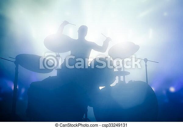 Drummer tocando la batería en conciertos de música. Luces del club - csp33249131