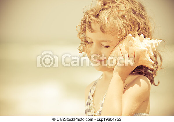 Niño feliz escucha conchas marinas en la playa - csp19604753