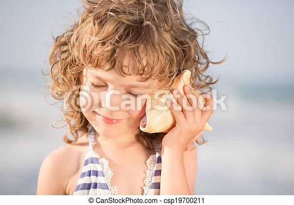Niño feliz escucha conchas marinas en la playa - csp19700211
