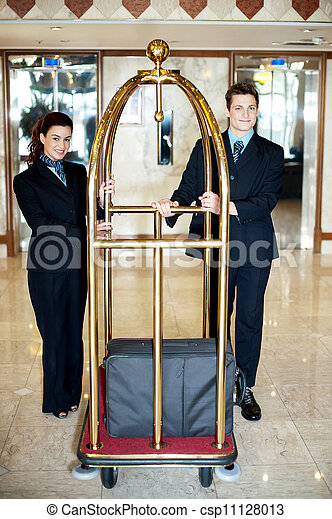Concierge colleagues holding baggage cart - csp11128013