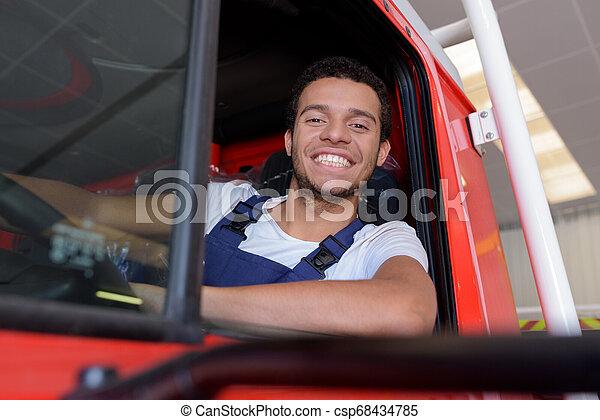 Retrato de un joven bombero feliz conduciendo un camión de bomberos en la estación - csp68434785