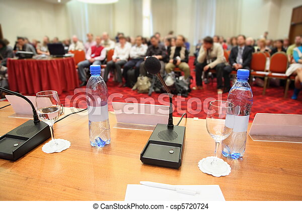 conference in hall. bottle, microphone, glass and pen on a table. focus on device in centre - csp5720724