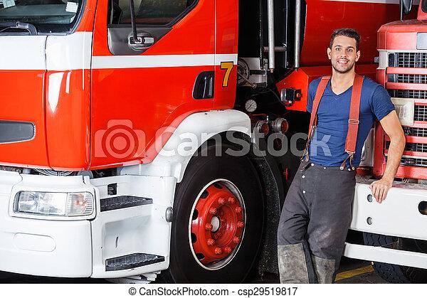 Bombero confiado apoyado en el camión - csp29519817