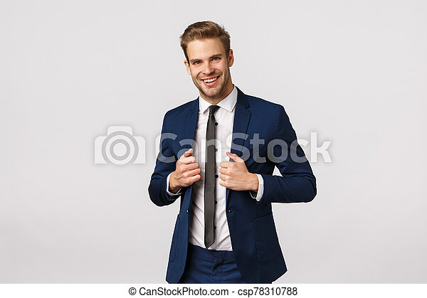 Confidence, elegance and business concept. Handsome young stylish businessman in suit, adjusting jacket and smiling, signed great deal and feeling success coming his hands, white background - csp78310788