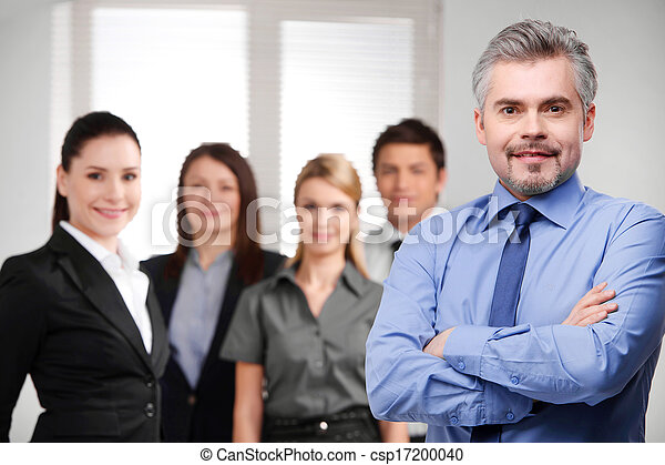 Confident adult businessman looking successful with crossed arms. Blur smiling business team on background  - csp17200040