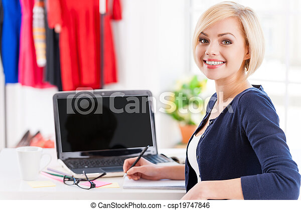 Confident and creative. Beautiful young woman looking over shoulder and smiling while sitting at her working place - csp19747846