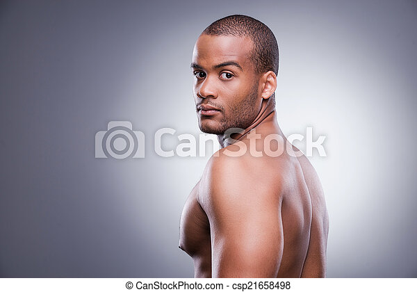 Confident and handsome. Young shirtless African man looking over shoulder while standing against grey background - csp21658498