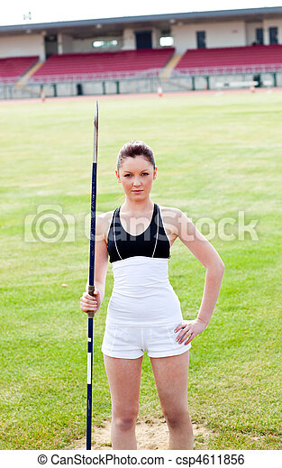 confident athletic woman ready to throw a javelin standing in a stadium looking at the camera - csp4611856