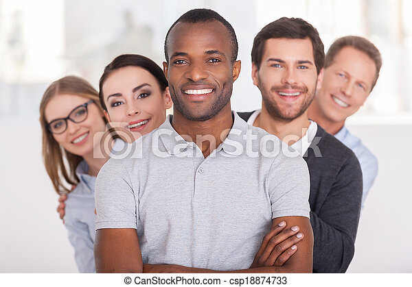 Confident business team. Cheerful young African man keeping arms crossed and smiling while group of people standing behind him in a row and looking at camera - csp18874733