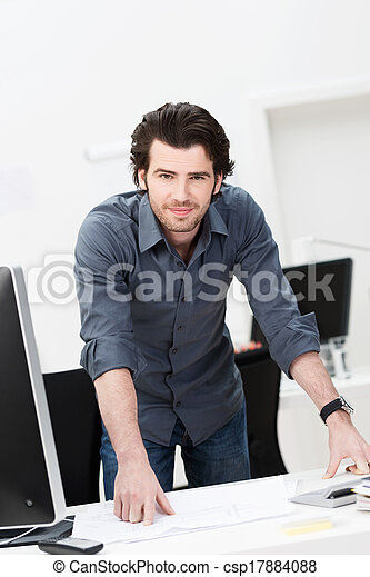 Confident businessman leaning on his desk - csp17884088